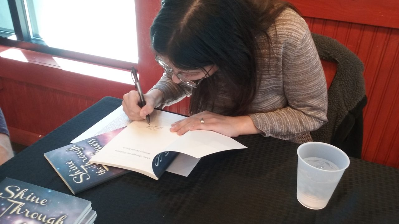 Author Brittany Nicole Lewis signing her book for a fan.